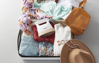 旅行バッグに衣類スチーマーを入れている写真です。